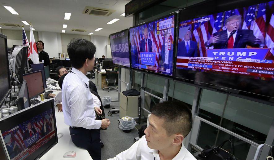 Money traders watch a news program at a foreign exchange brokerage in Tokyo, Wednesday, Nov. 9, 2016. (AP Photo/Shizuo Kambayashi)