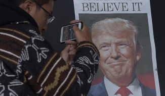 Zheng Gao of Shanghi, China, photographs the front pages of newspapers on display outside the Newseum in Washington, Wednesday, Nov., 9, 2016, the day after Donald Trump won the presidency. (AP Photo/Susan Walsh)