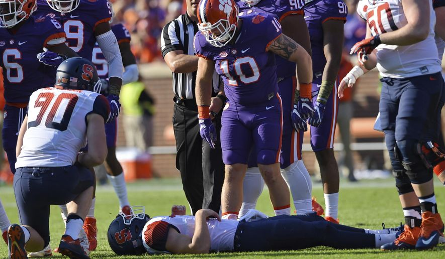 FILE - In this Nov. 5, 2016, file photo, Clemson's Ben Boulware (10) stands over Syracuse quarterback Eric Dungey after making a tackle during the first half of an NCAA college football game, in Clemson, S.C. Boulware, along with DT Dexter Lawrence and DL Christian Wilkins have combined for 171 tackles, 22.5 tackles for a loss, and 9.5 sacks.  (AP Photo/Richard Shiro, File)