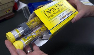 FILE - In this July 8, 2016, file photo, a pharmacist holds a package of EpiPen epinephrine auto-injectors, a Mylan product, in Sacramento, Calif. On Wednesday, Nov. 9, 2016, Mylan Inc. reported company earnings. (AP Photo/Rich Pedroncelli, File)