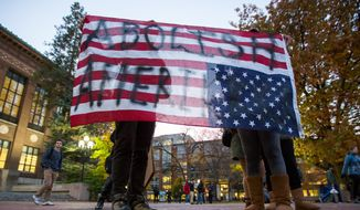 "Two people hold an American Flag upside down, which reads, ""Abolish Amerikkka"" during an anti-Trump rally at the Diag on the University of Michigan's campus on Wednesday, Nov. 9, 2016. Later in the evening about 1,00 people gathered at the Diag for a gathering promoting love, equality, and surprise of the recent election of Donald Trump. (Matt Weigand/The Ann Arbor News via AP)"