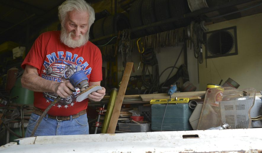 ADVANCE FOR THE WEEKEND OF NOV. 12-13 AND THEREAFTER - In an Oct. 3, 2016 photo, Sonny Buskirk readies his sander as he builds a bench from the tailgate of an old International at his shop, in Sheridan, Wyoming. Buskirk makes furniture from various car parts, street signs and other items from his salvage business. (Justin Sheely/Sheridan Press via AP)