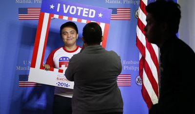 A Filipino student poses for a free souvenir photo after casting his ballot in a mock U.S. elections sponsored by the US Embassy Wednesday, Nov.9, 2016 in suburban Pasay city southeast of Manila, Philippines.(AP Photo/Bullit Marquez)