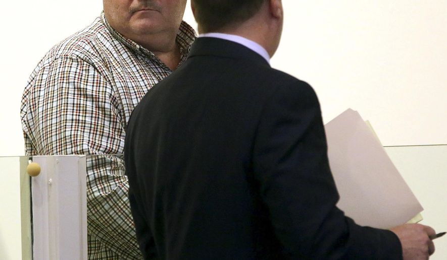 Police officer Brian Butler, left, stands with his attorney Randy Chapman during arraignment Wednesday, Nov. 9, 2016, in district court in Salem, Mass. Butler, who is charged with sexually assaulting a man in a station closet, is the husband of the Salem Police Chief Mary Butler. (Ken Yuszkus/The Salem News via AP, Pool)
