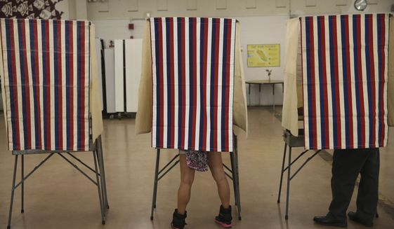 Voters cast their ballots in booths at Farrington High School, Tuesday, Nov. 8, 2016, in Honolulu. (AP Photo/Marco Garcia) **FILE**