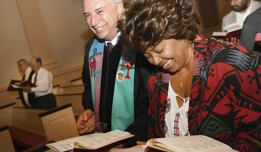 In this Tuesday, Nov. 8, 2016 photo, the Rev. Dr. James L. Brewer-Calvert, left, and Sylvia Gibbs sing during the Ecumenical Election Day Communion Service at the Decatur First United Methodist Church in Decatur, Ga. Democrats and Republicans shared the same pews, wearing voter stickers shaped like Georgia peaches, and shut out the barrage of news sweeping the country. (AP Photo/Rebecca Breyer)