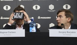 Chess world champion Magnus Carlsen, of Norway, left, looks through a virtual reality viewer while his challenger, Sergey Karjakin, of Russia, looks on during a news conference to promote the World Chess Championship in New York, Thursday, Nov. 10, 2016. The championship, which will also be broadcast live in 360 degrees, starts Nov. 11, 2016, in New York. (AP Photo/Seth Wenig)