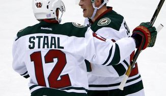 CORRECTS THAT SUTER HAD AN ASSIST ON THE GOAL, RATHER THAN SCORED THE GOAL - Minnesota Wild's Ryan Suter, right, celebrates his assist on a goal by Charlie Coyle with Eric Staal (12) during the first period of an NHL hockey game against the Pittsburgh Penguins in Pittsburgh, Thursday, Nov. 10, 2016. (AP Photo/Gene J. Puskar)