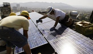 FILE - In this March 23, 2010, file photo, installers from California Green Design install solar electrical panels on the roof of a home in Glendale, Calif. The Obama administration is boosting the development of solar and wind energy on public lands. A final rule announced by the Interior Department on Thursday, Nov. 10, 2016, would create a new leasing program on public lands and encourage development in areas where it would have fewer effects on the environment.  (AP Photo/Reed Saxon, File)