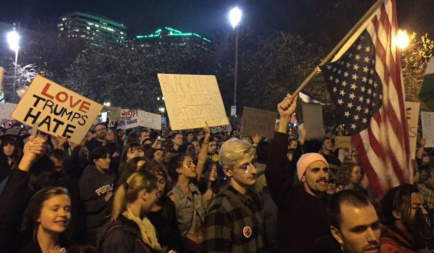 Protesters march on their way to Waterfront Park in Portland, Ore., on the third day of protests over the results of the 2016 U.S. presidential election, Thursday, Nov. 10, 2016. President-elect Donald Trump fired back on social media after demonstrators in both red and blue states hit the streets for another round of protests, showing outrage over the Republican's unexpected win. (Jim Ryan/The Oregonian via AP)