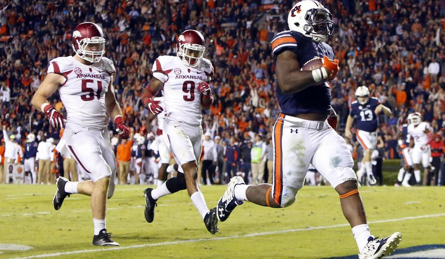 FILE - In this Oct. 22, 2016, file photo, Auburn running back Kamryn Pettway (36) scores a touchdown as he beats Arkansas linebacker Brooks Ellis (51) and defensive back Santos Ramirez (9) to the end zone during the second half of an NCAA college football game in Auburn, Ala. The status of Pettway, the No. 4 rusher in the nation, remains a mystery due to a left leg injury as the No. 8 Tigers try to protect their SEC title hopes in a game Saturday, Nov. 12, 2016, at Georgia. (AP Photo/Butch Dill, File)