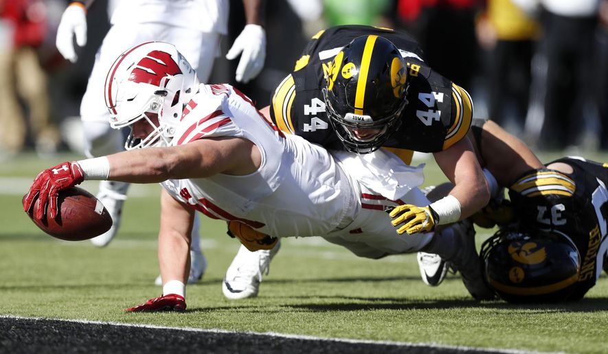 FILE - In this Oct. 22, 2016, file photo, Wisconsin tight end Troy Fumagalli dives across the goal line ahead of Iowa's Ben Niemann (44) and Brandon Snyder, right, on a 17-yard touchdown reception during an NCAA college football game in Iowa City, Iowa. Doubted nearly every week this season, the Badgers can win the Big Ten West Division if they win their final three regular season games. It would give Wisconsin a berth in the Big Ten title game, with the playoffs potentially in reach.The Badgers should be favored in each of their final three games. (AP Photo/Charlie Neibergall, File)