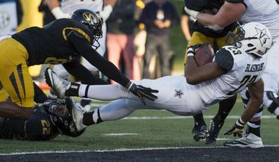 Vanderbilt running back Khari Blasingame, right, scores as he falls into the end zone ahead of the tackle from Missouri's Thomas Wilson, top left, and Anthony Sherrils, bottom left, during the second quarter of an NCAA college football game Saturday, Nov. 12, 2016, in Columbia, Mo. (AP Photo/L.G. Patterson)