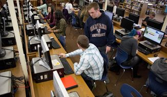 ADVANCE FOR USE SATURDAY, NOV. 12 - In this Tuesday, Nov. 1, 2016 photo, school counselor Dan Hawkes helps seniors with their college applications  during the Idaho Board of Education's College Application Week at Twin Falls High School in Twin Falls, Idaho. (Pat Sutphin/The Times-News via AP)