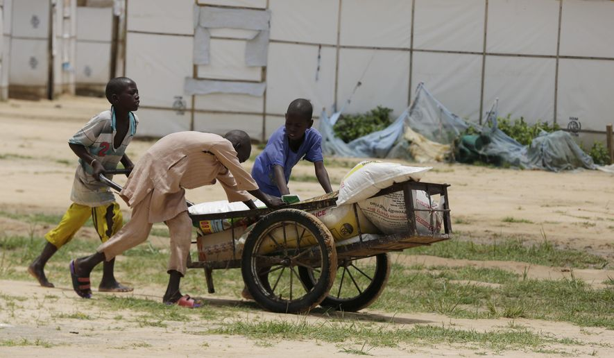 Children displaced by Islamist extremists wheel food handed out to them at the Bakassi camp in Maiduguri, Nigeria, amid allegations that officials have diverted aid intended for Boko Haram refugees. (Associated Press/File)