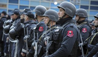 """Albanian police get ready in front of the Elbasan Arena, where will Albania play their World Cup 2018 qualifying soccer match against Israel under tight security measures in Elbasan, 50 kilometers (30 miles) south of the capital, Tirana, Saturday, Nov. 12, 2016. Police have taken extreme steps after media reports that an alleged terror group of 15 persons, arrested in Albania, Kosovo and Macedonia, planned an attack during the match. The venue was changed for """"security reasons"""" from the northern city of Shkoder to Elbasan (AP Photo/Hektor Pustina)"""