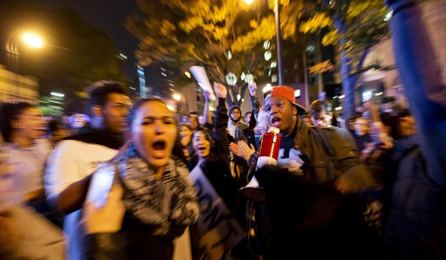 In this photo taken with a zoom effect, protesters march in the street to demonstrate against the election of President-elect Donald Trump in Atlanta, Friday, Nov. 11, 2016. Spurred by fear and outrage, protesters around the country rallied and marched Friday as they have done daily since Donald Trump's presidential election victory. (AP Photo/David Goldman)