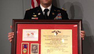U.S. Army Lt. Col. Matthew Yandura holds Robert Mathis' Purple Heart medal and certificate Sunday, Nov. 13, 2016, in Farmington Hills, Mich. The medal and certificate are to be presented to Mathis' relatives Sunday during a ceremony at the Holocaust Memorial Center Zekelman Family Campus in Farmington Hills, northwest of Detroit. Mathis was killed during World War II. Yandura found Mathis' Purple Heart certificate in 2013 in a used map shop in Jerusalem. The Purple Heart will be returned to Mathis' family in a ceremony on Sunday. (AP Photo/Corey Williams)
