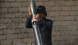 An Iraqi soldier fires a mortar against the Islamic State militants east of Mosul on Monday. A suicide bombing in Iraq targeted the Shiite sacred city of Karbala on Monday, killing at least six civilians. In Fallujah, two Iraqi police officers were killed in another bombing. Iran appears to be claiming a greater role in the battle to oust the Islamic State terrorists. (Associated Press)