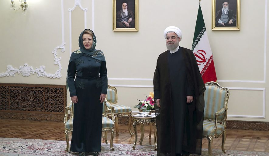 In this photo released by official website of the office of the Iranian Presidency, President Hassan Rouhani, right, stands with Russian Federation Council Speaker Valentina Matviyenko after welcoming her as he waits to welcome members of the Russian delegation, at his office in Tehran, Iran, Monday, Nov. 14, 2016. Portraits of the late Iranian revolutionary founder Ayatollah Khomeini, left, and Supreme Leader Ayatollah Ali Khamenei hang on the wall. (Iranian Presidency Office via AP)