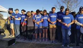 """In this Saturday, Nov. 12, 2016, photo, supporters link arms around a group of Hispanic demonstrators at the Immigration and Customs Enforcement detention center in Aurora, Colo., after an 11-mile prayer walk to show solidarity with immigrants. Several hundred people marched from Denver to Aurora on Saturday to urge the new Trump administration and Congress to work together to solve problems with immigration, saying they """"want to build bridges, not walls."""" (AP Photo/Steven K. Paulson)"""