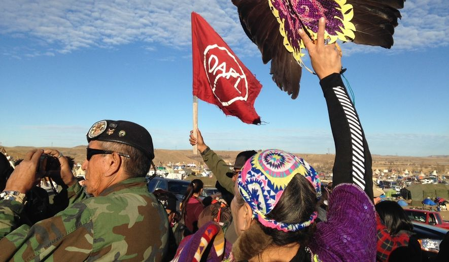 Demonstrators against the Dakota Access oil pipeline hold a ceremony at the main protest camp Tuesday, Nov. 15, 2016, near Cannon Ball, North Dakota. The ceremony was in honor of Robert F. Kennedy Jr., an environmental attorney and president of the New York-based Waterkeeper Alliance, who visited the Dakota Access oil pipeline protesters Tuesday. (AP Photo/James MacPherson)