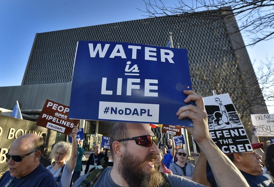 People including Steve Cramer, center, protest the Dakota Access pipeline project in front of the Richard Bolling Federal Building on Tuesday, Nov. 15, 2016, in downtown Kansas City, Mo. The company building a $3.8 billion oil pipeline sought a federal judge's permission Tuesday to circumvent President Barack Obama's administration and move ahead with a disputed section of the project in North Dakota, as opponents held protests across the country urging it to be rejected. (Keith Myers/The Kansas City Star via AP)