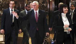 Vice President-elect Mike Pence waves to the media as he leaves Trump Tower with his wife Karen, Tuesday, Nov. 15, 2016, in New York. (AP Photo/Carolyn Kaster)