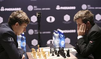 Chess world champion Magnus Carlsen, right, of Norway, and challenger Sergey Karjakin, of Russia, study the board during the fourth round of the World Chess Championship in New York, Tuesday, Nov. 15, 2016. (AP Photo/Seth Wenig)