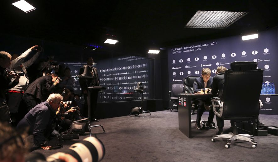 Chess world champion Magnus Carlsen, right, of Norway, and challenger Sergey Karjakin, of Russia, study the board while members of the media record their first moves during the fourth round of the World Chess Championship in New York, Tuesday, Nov. 15, 2016. (AP Photo/Seth Wenig)
