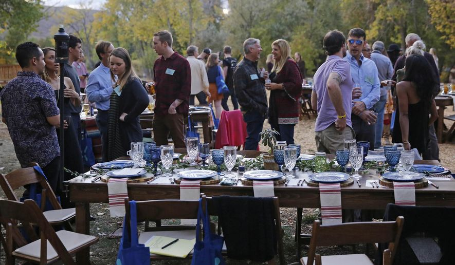 FILE - In this Oct. 2, 2016, file photo, diners chat and smoke marijuana, before eating dishes prepared by chefs during an evening of pairings of fine food and craft marijuana strains served to invited guests dining at Planet Bluegrass, an outdoor venue in Lyons, Colo. Chefs and pot growers trying to explore fine dining with weed face a legal gauntlet to make pot dinners a reality, even where the drug is legal. Denver has approved a first-in-the-nation law allowing people to use marijuana in bars and restaurants. Denver voters weighed in on Proposition 300 as eight other states legalized marijuana for medical or recreational purposes last week. (AP Photo/Brennan Linsley, File)