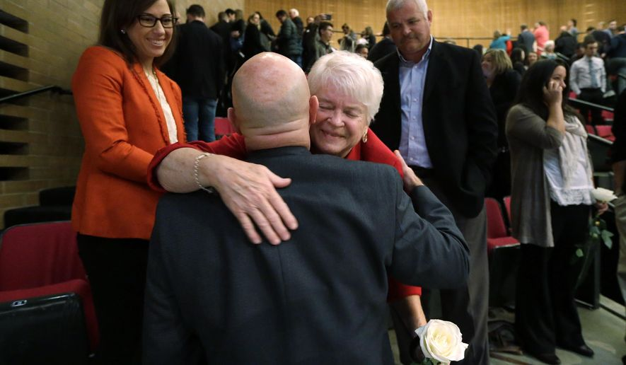Barronelle Stutzman, center, a florist who was fined for denying service to a gay couple in 2013, holds a flower as she embraces a supporter after a hearing before Washington's Supreme Court, Tuesday, Nov. 15, 2016, in Bellevue, Wash. Stutzman was sued for refusing to provide services for a same sex-wedding and says she was exercising her First Amendment rights, but justices questioned whether ruling in her favor would mean other businesses could turn away customers based on racial or other grounds. (AP Photo/Elaine Thompson) **FILE**