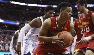 Maryland's Anthony Cowan, center, with teammate Ivan Bender, right, holds the ball during the second half of an NCAA college basketball game in Washington, Tuesday, Nov. 15, 2016. Maryland won 76-75. (AP Photo/Manuel Balce Ceneta)