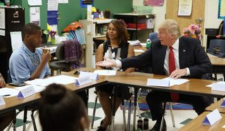 FILE - In this Sept. 8, 2016, file photo, then=Republican presidential candidate Donald Trump reaches to shake hands with Egunjobi Songofunmi during a meeting with students and educators before a speech on school choice at Cleveland Arts and Social Sciences Academy in Cleveland.  (AP Photo/Evan Vucci, File) **FILE**