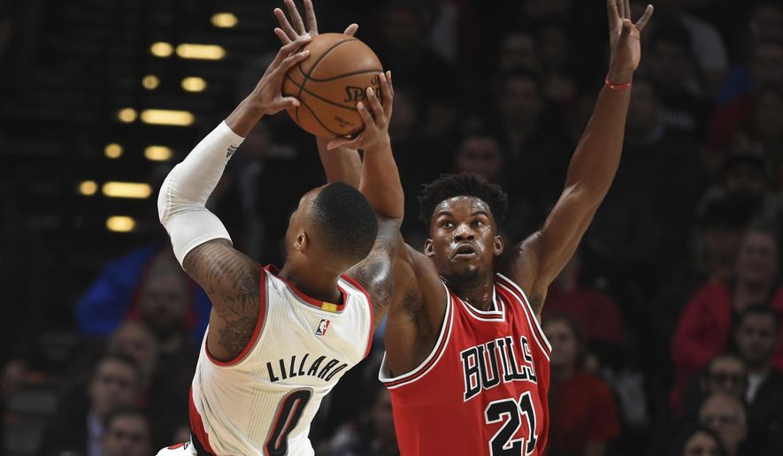Chicago Bulls forward Jimmy Butler goes up to try to block the shot of Portland Trail Blazers guard Damian Lillard during the first quarter of an NBA basketball game in Portland, Ore., Tuesday, Nov. 15, 2016. (AP Photo/Steve Dykes)