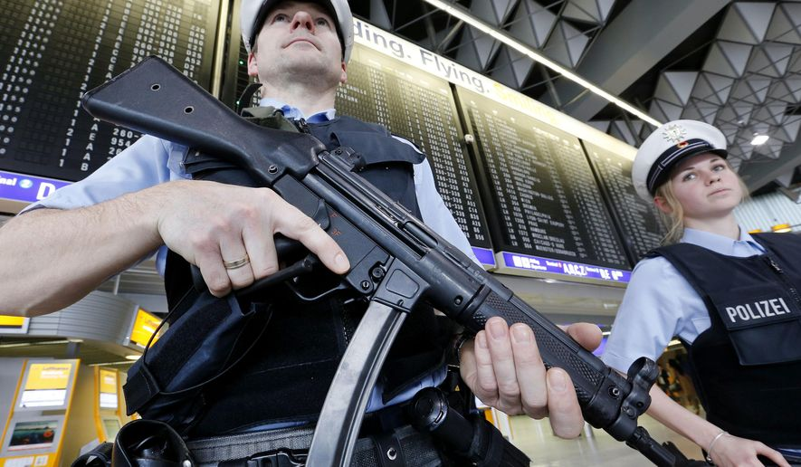 German police officers guard a terminal at the airport in Frankfurt, Germany, after security measures were increased after the Belgium attacks the previous day, March 23, 2016. (AP Photo/Michael Probst, File) ** FILE **
