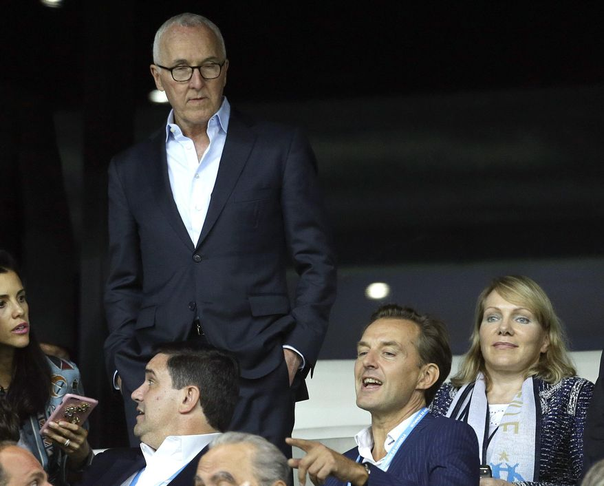FILE - In this Sept. 18, 2016 file photo, USA's Frank McCourt, standing, is seen with former owner of Olympique Marseille Margarita Louis Dreyfus, right, in the Velodrome Stadium, in Marseille, southern France. Frank McCourt's plans to bring Marseille back to the top of French and European soccer could be undermined by local criminals. (AP Photo/Claude Paris, File)