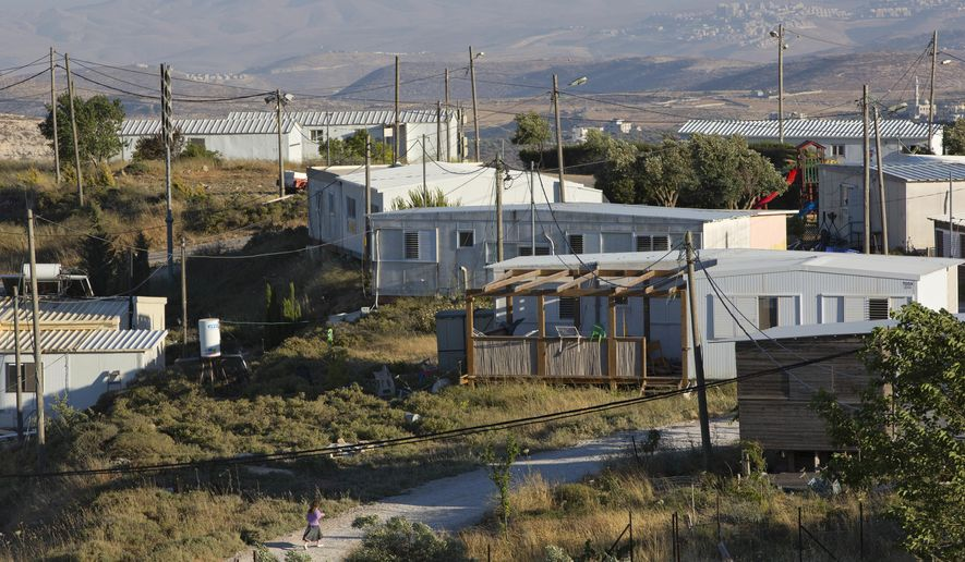 FILE - In this Wednesday, May 18, 2016 file photo, Amona, an unauthorized Israeli outpost in the West Bank, is seen east of the Palestinian town of Ramallah. On Wednesday, Nov. 16, 2016, The Israeli parliament has given preliminary approval to a proposal that would legalize hundreds of homes built in West Bank settlements that sit on private Palestinian land. (AP Photo/Oded Balilty, File)