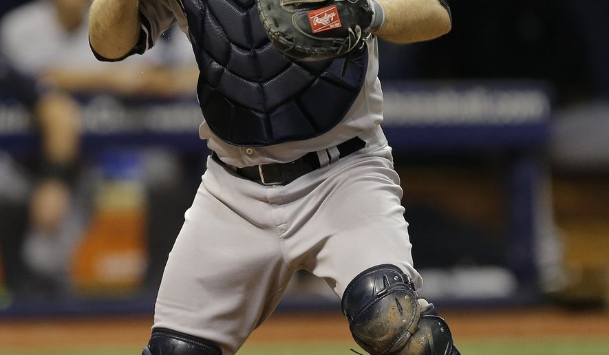 FILE - In this Monday, Sept. 14, 2015 file photo, New York Yankees catcher Brian McCann loses the baseball after forcing Tampa Bay Rays' Asdrubal Cabrera at home plate on a fielder's choice by Kevin Kiermaier during the second inning of a baseball game in St. Petersburg, Fla. The New York Yankees traded veteran catcher Brian McCann and $11 million to the Houston Astros on Thursday, Nov. 17, 2016 for a pair of young minor league pitchers.(AP Photo/Chris O'Meara, File)