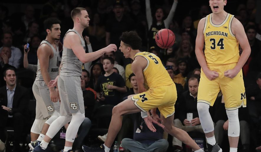 Michigan forward Mark Donnal (34) and forward D.J. Wilson (5) react after a dunk by Wilson against Marquette in the second half of an NCAA college basketball game, Thursday, Nov. 17, 2016, in New York. (AP Photo/Julie Jacobson)