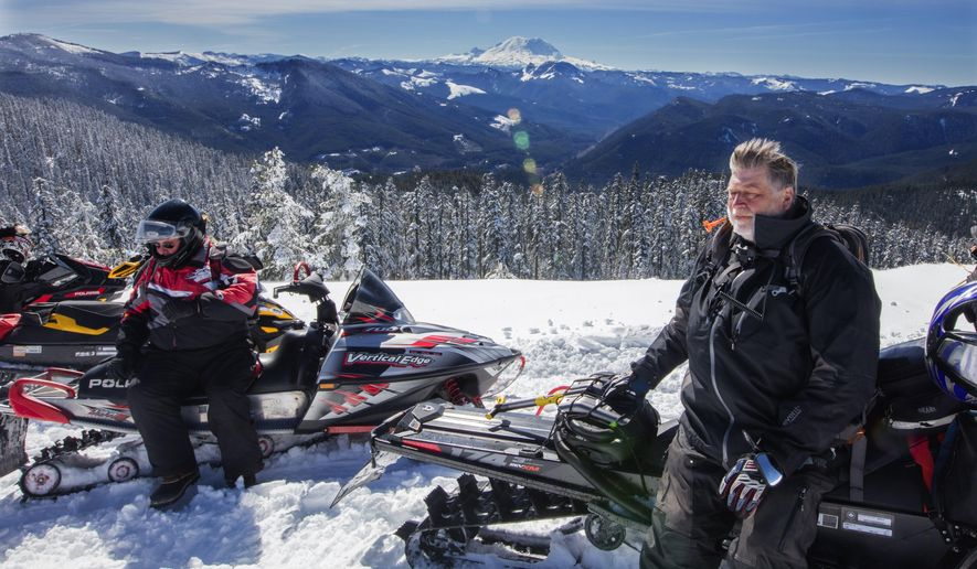 In this Tuesday, March 17, 2016 photo, Bob Seelye and Mick Steinman sit on their snowmobiles on the very top viewpoint of the trail system near Crystal Springs Sno-Park in Wash. Mount Rainier in the distance.  (Steve Ringman/The Seattle Times via AP)