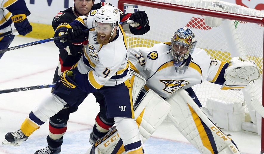 Nashville Predators' Ryan Ellis (4) battles in front of the net with Ottawa Senators' Chris Neil (25) as goaltender Pekka Rinne looks on during the second period of an NHL hockey game, Thursday, Nov. 17, 2016 in Ottawa, Ontario. (Fred Chartrand/The Canadian Press via AP)