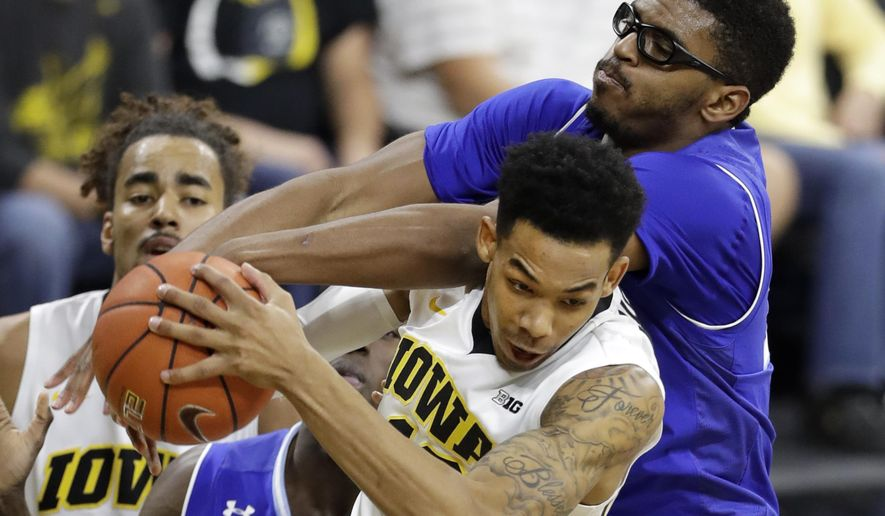 Iowa guard Christian Williams grabs a rebound in front of Seton Hall forward Rashed Anthony, right, during the first half of an NCAA college basketball game, Thursday, Nov. 17, 2016, in Iowa City, Iowa. (AP Photo/Charlie Neibergall)