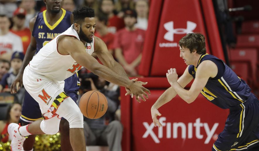 Maryland forward Damonte Dodd, left, and St. Mary's of Maryland guard Brendan Cavanagh chase after a loose ball in the first half of an NCAA college basketball game, Thursday, Nov. 17, 2016, in College Park, Md. (AP Photo/Patrick Semansky)
