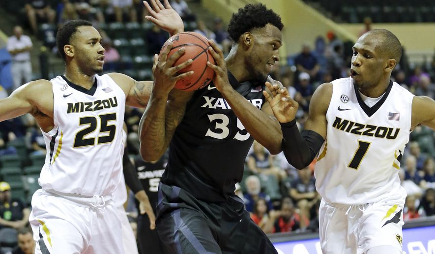 Xavier's RaShid Gaston (35) looks to pass the ball after he is caught between Missouri's Russell Woods (25) and Terrence Phillips (1) during the first half of the Tire Pros Invitational NCAA college basketball game, Thursday, Nov. 17, 2016, in Kissimmee, Fla. (AP Photo/John Raoux)