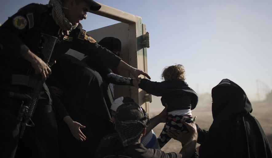 A baby displaced by fighting between Iraqi forces and Islamic state militants is carried into the back of a truck before leaving Mosul, Iraq, Friday, Nov. 18, 2016. (AP Photo/Felipe Dana)