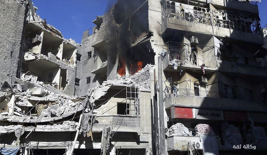 This image released by Thiqa News Agency shows smoke rising and fires still burning after airstrikes hit the Al-Shaar neighborhood of Aleppo, Syria, Friday, Nov. 18, 2016. Intensive bombings pummeled Syria's rebel-held eastern neighborhoods of the city of Aleppo on Friday, residents and rescuers said, hitting an area housing several hospitals and sending the chief of a pediatrics clinic in a frantic search for a place to move his young patients. (Thiqa News via AP)