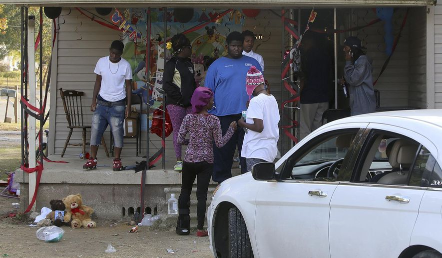 People gather at the scene of a shooting in Dyersburg, Tenn., on Friday, Nov. 18, 2016.  Authorities say they've arrested a man accused of fatally shooting the mother of a 2-year-old during the child's birthday party in western Tennessee. Dyersburg, Tennessee, Police Chief Steven Isbell said 30-year-old Torius Russell was charged Friday morning with first-degree murder. (C.B. Schmelter/The Jackson Sun via AP)