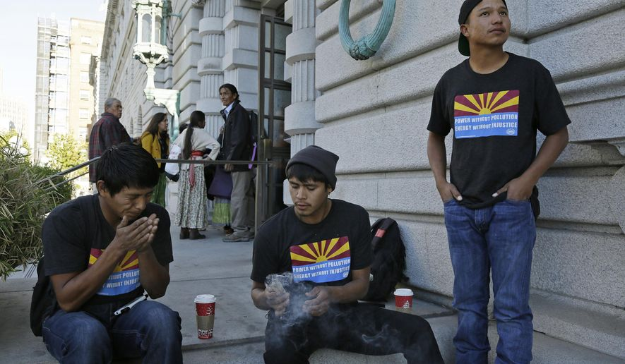 Navajo youths from left, Robert Yazzie, Sedate Tsosie and Sheldon Natoni burn sage as tribal members in the background enter the United States Court of Appeals for the Ninth Circuit in San Francisco on Friday, Nov. 18, 2016. Thirty Navajo youths have traveled from their reservation in Arizona to San Francisco to protest a federal decision that would allow a massive coal-fired power near their homes to bypass pollution-control regulations for the next several decades. (AP Photo/Eric Risberg)