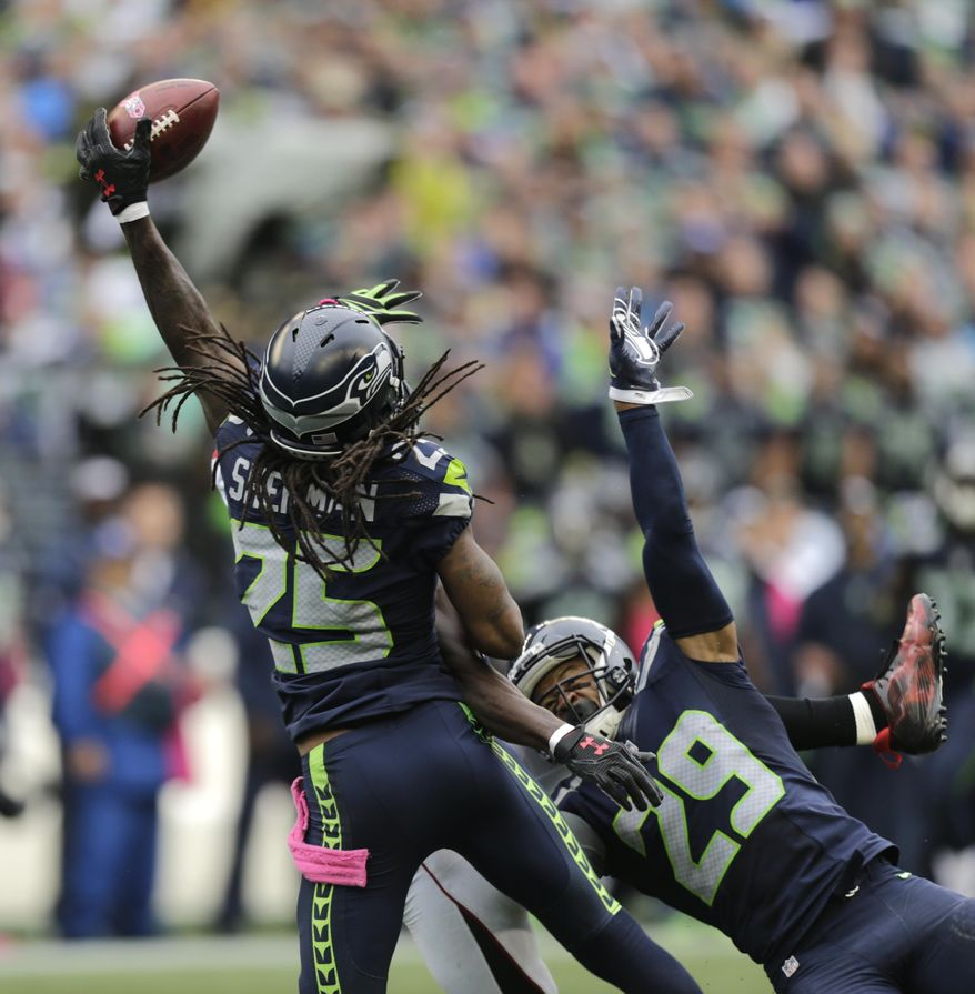 FILE -  In this Sunday, Oct. 16, 2016 file photo, Seattle Seahawks cornerback Richard Sherman (25) and Earl Thomas (29) break up a pass intended for Atlanta Falcons wide receiver Julio Jones in the second half of an NFL football game, in Seattle. The duo of Earl Thomas and strong safety Kam Chancellor are just two of the challenges Philadelphia Eagles' rookie Carson Wentz has to face when the Philadelphia Eagles travel to Seattle on Sunday, Nov. 20, 2016. (AP Photo/Stephen Brashear, File)